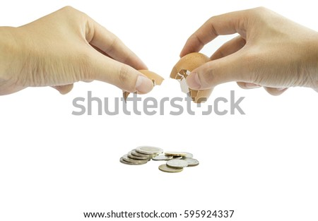hands cracking an egg  with money flow on white background .