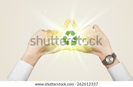 Hands creating a form with green recycling sign in the center