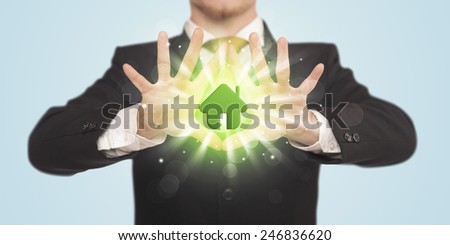 Hands creating a form with shining green house in the center  - stock photo