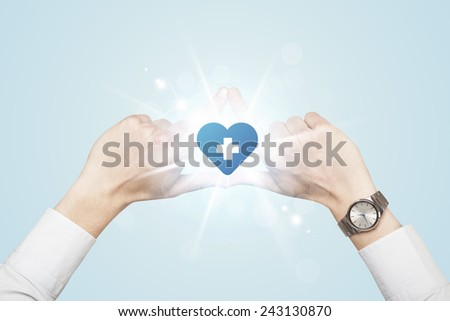 Hands creating a form with shining heart blue cross in the center - stock photo