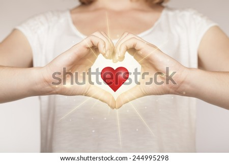 Hands creating a form with shining red heart in the center