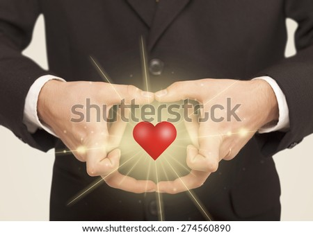 Hands creating a form with shining red heart in the center - stock photo