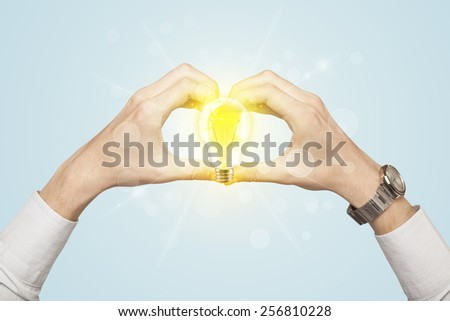 Hands creating a form with yellow light bulb in the center - stock photo