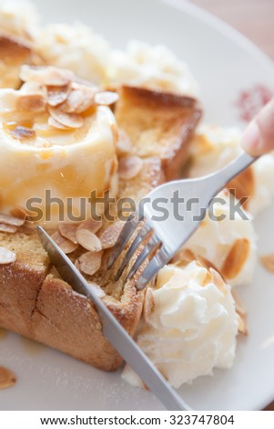 Hands cut bread. Bread, ice cream Are cut with a knife and beaten. - stock photo