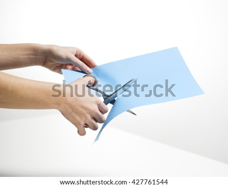HANDS CUTTING A BLUE PAPER WITH SCISSORS ON WHITE BACKGROUND - stock photo