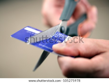 Hands cutting a credit card with scissors - stock photo