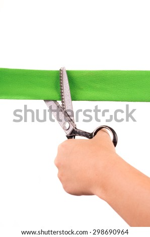 hands cutting green ribbon with scissors - stock photo