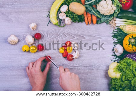 Hands cutting vegetables with a knife on wooden table  - stock photo