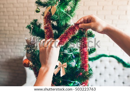 Hands decorating Christmas tree with red tinsel. Close-up of green pine-tree decorated with sparkling trumpery and bows. Holiday, winter, happiness concept