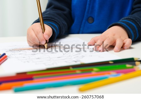 hands detail of a young children coloring drawing with multicolored pencils - stock photo