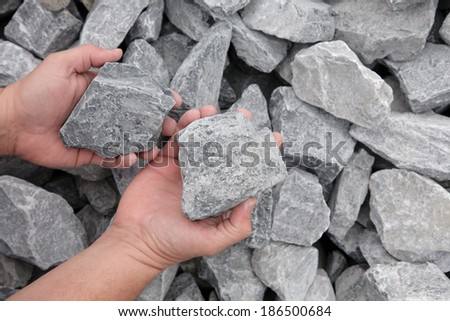 Hands displaying limestone landscaping rocks - stock photo