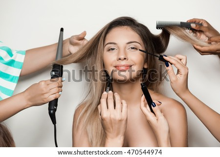 Hands doing hairstyle and make up young beautiful naked girl.