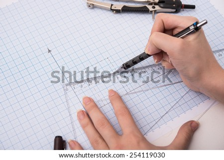 hands drawing a graphic  on graph paper