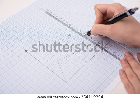 hands drawing a graphic  on graph paper - stock photo