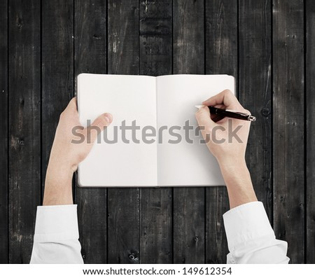hands drawing in notebook on gray table - stock photo