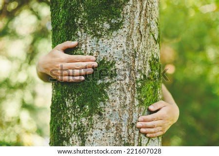 hands embracing a tree trunk - stock photo