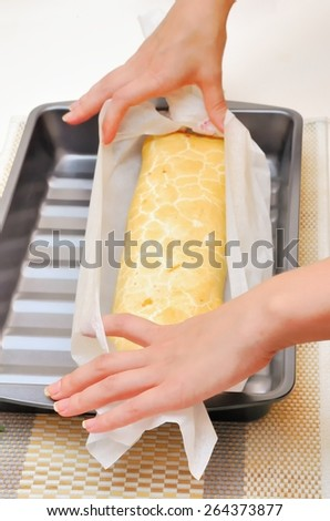 hands expand Swiss roll (cake) from parchment  in oven