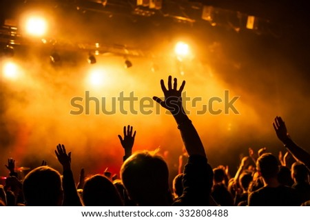 hands fans during a concert. - stock photo