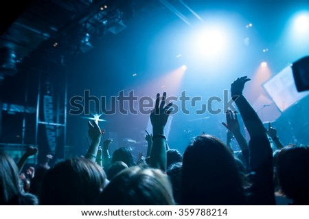 hands fans during a concert