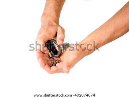 Hands filled with black pepper, isolated on white background .