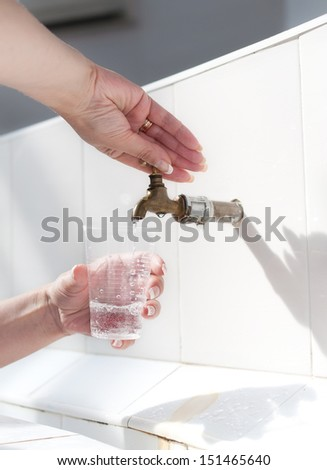 Hands filling mineral water plastic cup. - stock photo