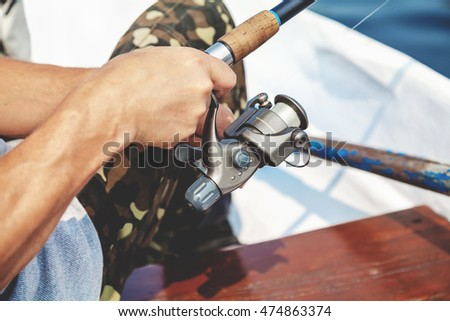 Hands fisherman keep spinning rod and rotate the handle fast-response spool close-up