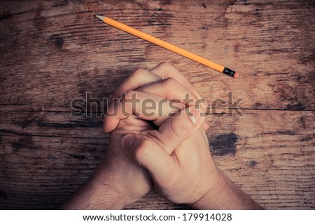 Hands folded in prayer on table with pencil - stock photo