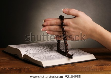 Hands folded in prayer over open russian Holy Bible - stock photo