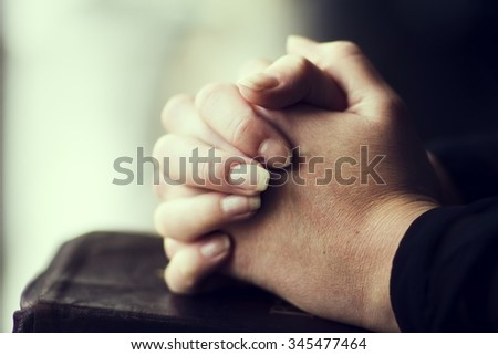 Hands folded together on leather Bible - stock photo