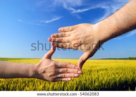 Hands form a rectangle against a wheaten field