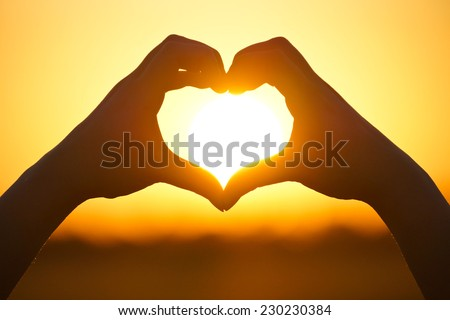 hands forming a heart shape with sunset silhouette - stock photo