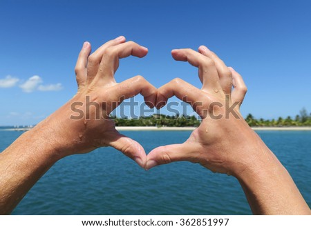 Hands forming heart. Tropical holiday concept with blue water and sky and a white sandy beach with palms in the back.