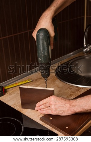 Hands furniture maker with a drill. - stock photo