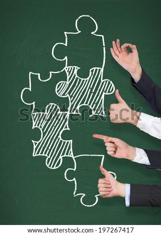 Hands, gesturing and puzzle pieces. Green board.