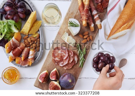 Hands getting an olive, cured meat charcuterie selection salami, chorizo, prosciutto wrapped bread sticks with fresh fig, rock melon, almonds and white wine - stock photo
