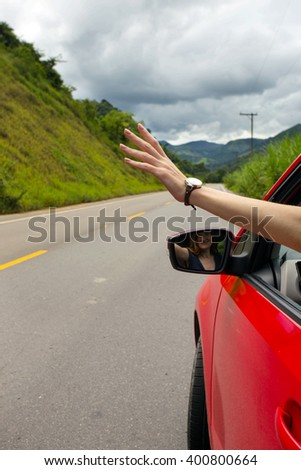 hands girl peering out of the car on a background of mountains, Brazil