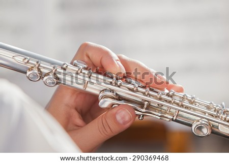 Hands girl playing a flute - stock photo