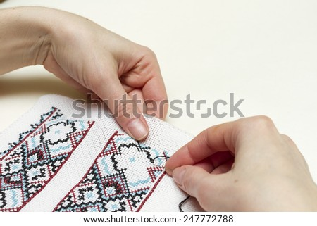 Hands girls embroider pattern cross. - stock photo