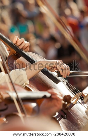 Hands girls playing the cello in the orchestra - stock photo