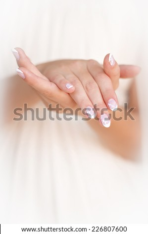 Hands girls with white manicure in white dress
