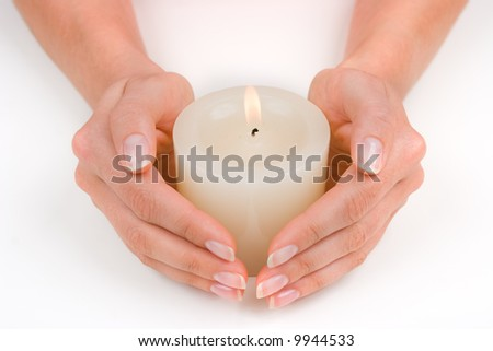 Hands guarding a white candle over white - stock photo