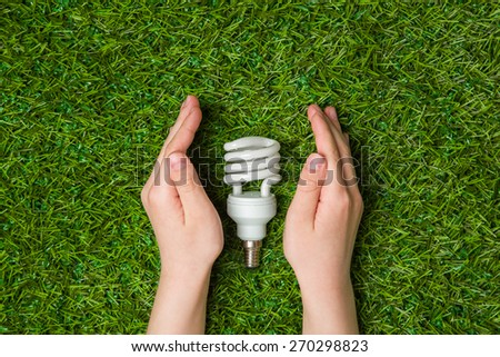 Hands guarding energy saving eco lamp close up