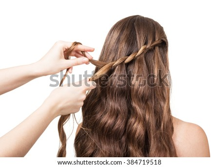 Hands hairdresser braided lock of the girl with long hair isolated on white background. - stock photo