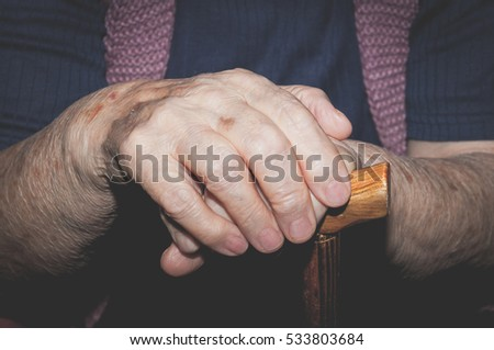 Hands. Hands of old lady with walking stick. Selective focus and light.