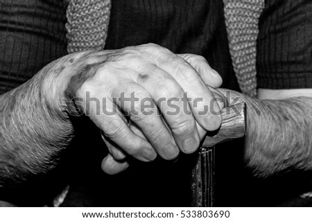 Hands. Hands of old lady with walking stick. Selective focus and light. Black and white.