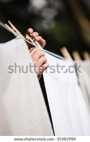 Hands hanging laundry on a clothesline outside