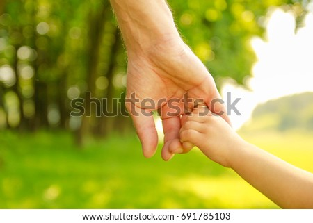 hands Happy parents and child outdoors in the park