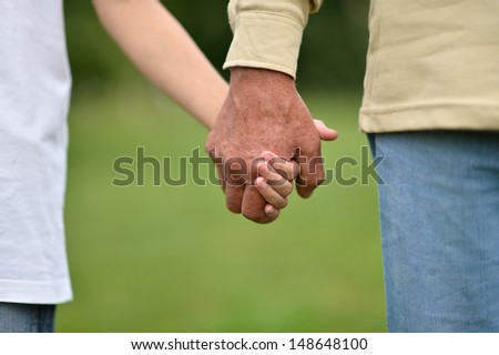 hands held together on a background of nature - stock photo