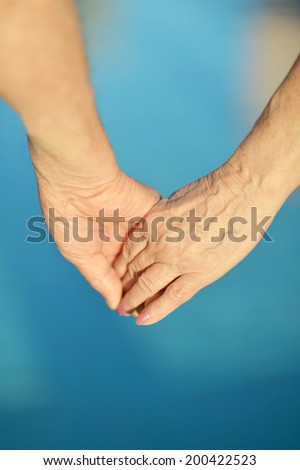 Hands held together on a blue background