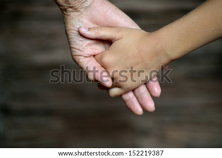 Hands held together on a natural dark background
